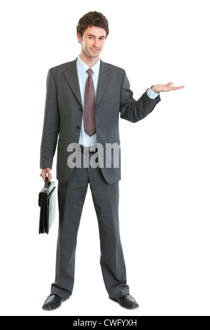 Businessman with briefcase presenting something on empty hand - Stock Photo