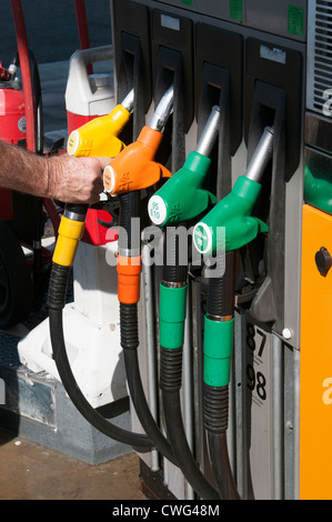 Selecting by colour fuel pump at a self service petrol station - Stock Photo