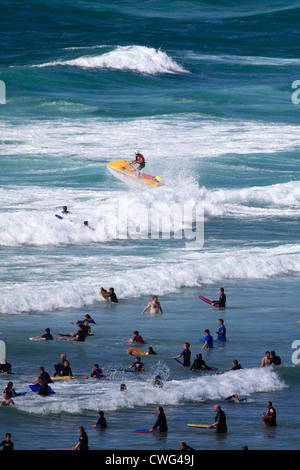 Surfers in the sea, Perranporth village, Cornwall County; England; UK - Stock Photo