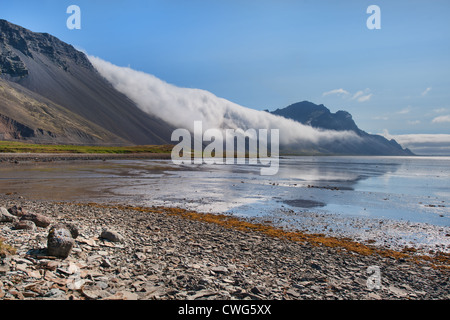 Clouds roll down from a mountain on Iceland's south coast near Höfn - Stock Photo