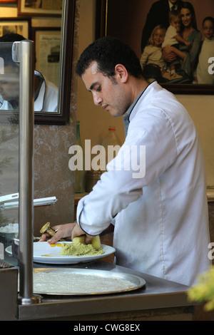 A young man preparing fresh falafel balls at the famous Al-Quds falafel restaurant in the Rainbow Street in Amman, - Stock Photo