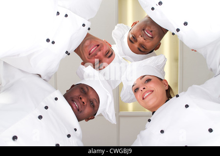 underneath of group of professional chefs heads together form a team - Stock Photo