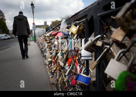 A man walks past thousands of padlocks on pont des arts over the River Seine, Paris - Stock Photo