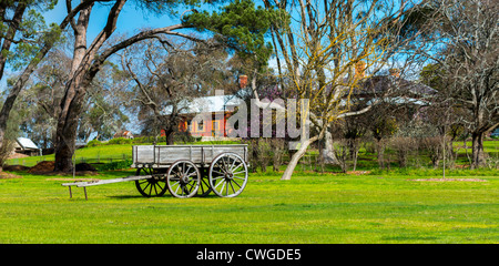 An Australian country farm with an old wagon in the field. - Stock Photo