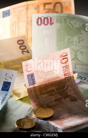 Euromuenzen on disarranged euro notes in various denominations - Stock Photo