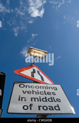 british road signs indicating a narrowing road and warning of oncoming vehicles in middle of road - Stock Photo