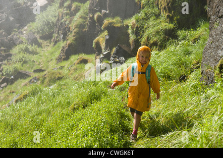 A young girl hiking a wet grassy slope, Rio Grande National Forest, Creede, Colorado. - Stock Photo
