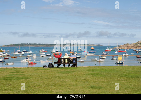 A group of people relax on a seat enjoying the view over Hugh Town Harbour , St Mary's, Isles of Scilly - Stock Photo