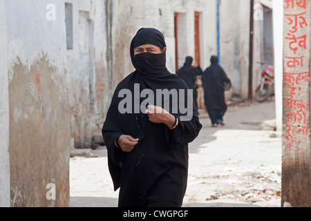 Muslim woman, covered completely in black burqa, walking the streets of Agra, Uttar Pradesh, India - Stock Photo