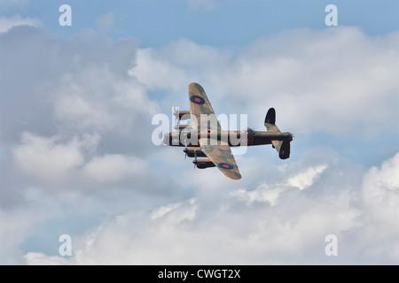 Avro Lancaster bomber of the Battle of Britain Memorial Flight, over-flying Little Gransden airfield. - Stock Photo