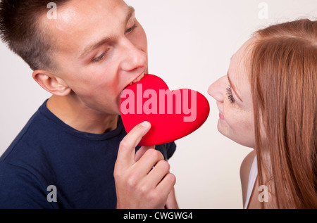 Young couple sharing a heart. - Stock Photo