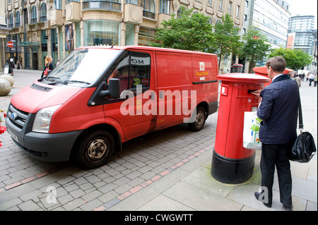 man posting mail in a royal mail post box with a royal mail van parked beyond 2012 - Stock Photo