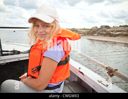 Little girl on a small boat wears bright orange life-jacket - Stock Photo