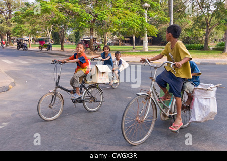 Horizontal portrait of a group of young Cambodian children riding on oversized bicycles down the road. - Stock Photo