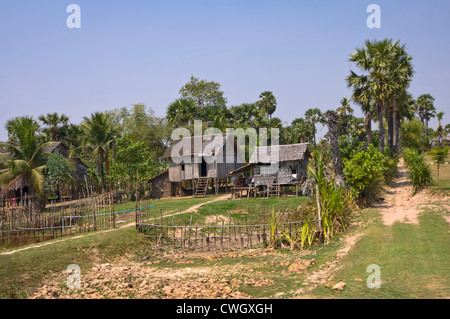 Horizontal wide angle view of a typical wooden house on stilts in rural Cambodia - Stock Photo