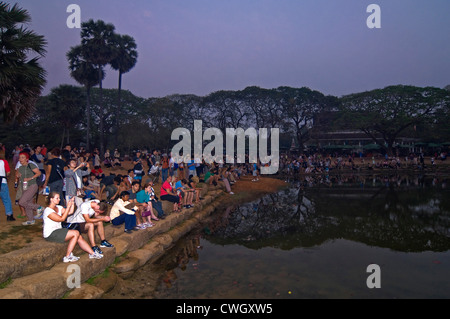 Horizontal view of tourists sitting together around a lake watching the sunrise over Prasat Angkor Wat. - Stock Photo