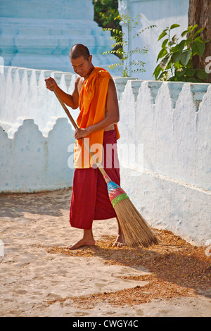 A MONK cleans the grounds of the TAUNG MIN GYI PAGODA in AMARAPURA the old Royal Capital 11 kilometers from MANDALAY - Stock Photo
