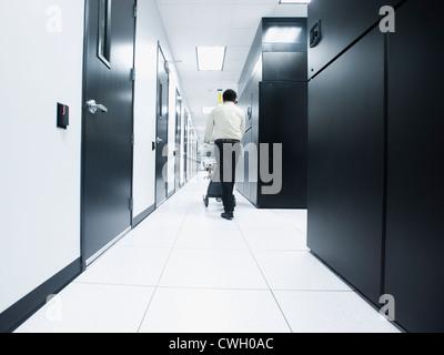 Asian businessman walking in server room