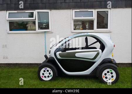 Electric car charging outside house at Hay on Wye, Powys, Wales, Cymru, UK - Stock Photo