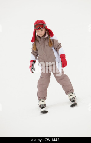 Young Girl Skiing Down Slope On Holiday In Mountains - Stock Photo