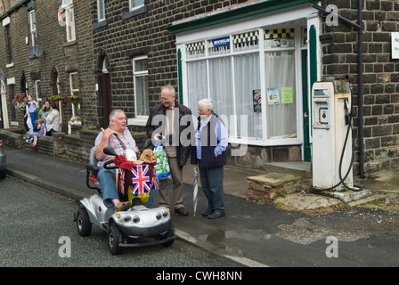 Mobility vehicle disabled man with dog using a mobility motorised decorated scooter talking with friends  UK HOMER - Stock Photo