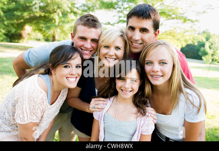 Large family gathered together smiling at the camera - Stock Photo