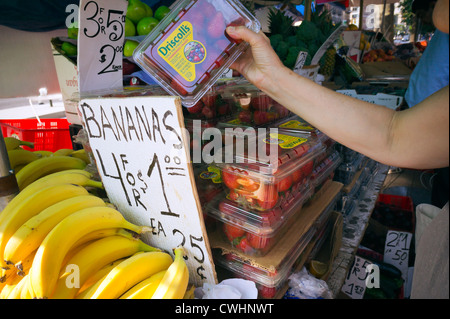 A shopper chooses her strawberries at a fruit and vegetable stand in the Chelsea neighborhood of New York - Stock Photo