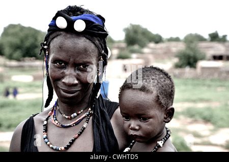 Peul woman wearing handmade jewelry with her baby, Mali - Stock Photo