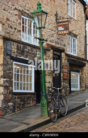 Bicycle by a leaning lamppost outside an old book shop in historic quarter of city of Lincoln, Lincolnshire, England, - Stock Photo