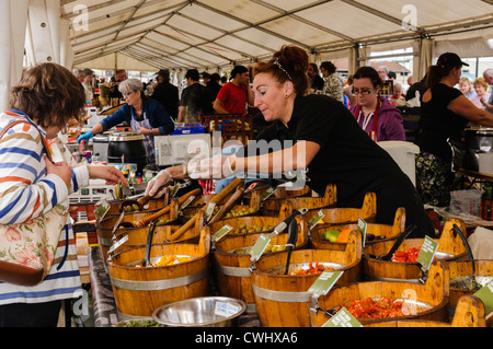 Woman buying olives at a market stall selling Mediterranean produce - Stock Photo
