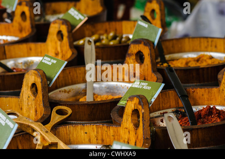 Mediterranean traditional food on sale at a market stall, including pesto, olives, tapenade, sundried tomatoes, - Stock Photo