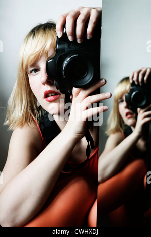 young woman,photographer,mirror image - Stock Photo
