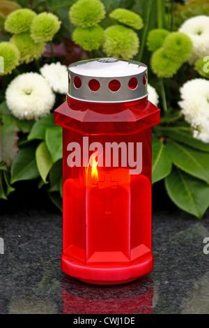 Illuminated votive candle glows on a grave lantern - Stock Photo
