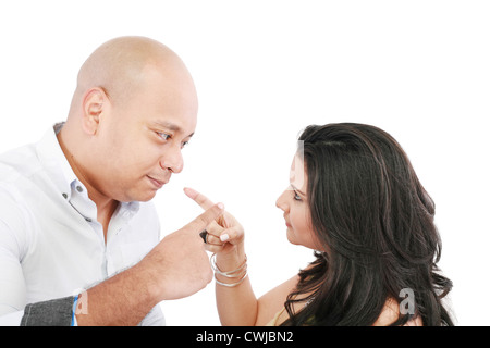 Young couple pointing at each other against a white background - Stock Photo