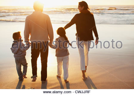 Family holding hands and walking on beach at sunset - Stock Photo