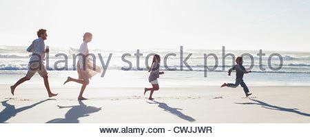 Family running on sunny beach - Stock Photo