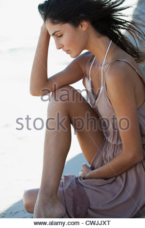 Pensive woman with head in hands - Stock Photo