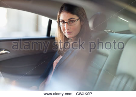 Portrait of confident businesswoman in back seat of car - Stock Photo