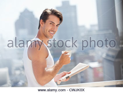 Portrait of smiling man drinking coffee and reading newspaper on urban balcony - Stock Photo