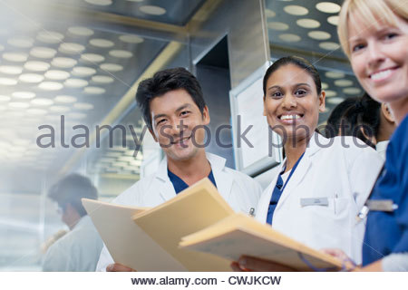 Portrait of smiling doctors and nurse with medical records - Stock Photo