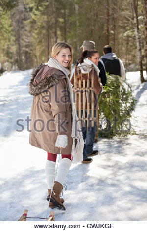 Portrait of friends with sleds and fresh cut Christmas tree in woods - Stock Photo