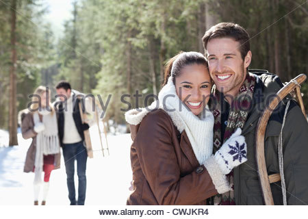 Portrait of smiling couple with sled in snowy woods - Stock Photo