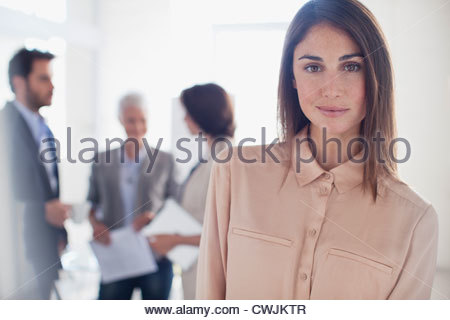 Portrait of smiling woman in office with co-workers in background - Stock Photo