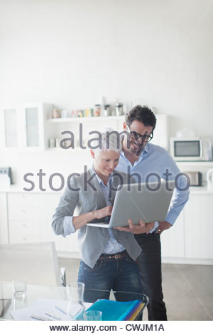 Businessman and businesswoman using laptop in office - Stock Photo
