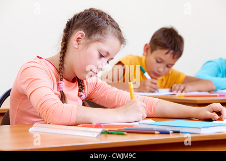 Portrait of lovely girl drawing in copybook with schoolboy on background - Stock Photo
