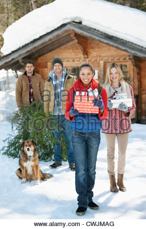 Portrait of smiling couples and dog with fresh cut Christmas tree and gifts in front of cabin - Stock Photo