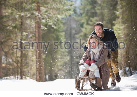 Man pushing woman on sled in snowy woods - Stock Photo