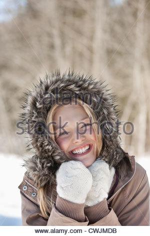 Portrait of smiling woman wearing fur hood coat - Stock Photo
