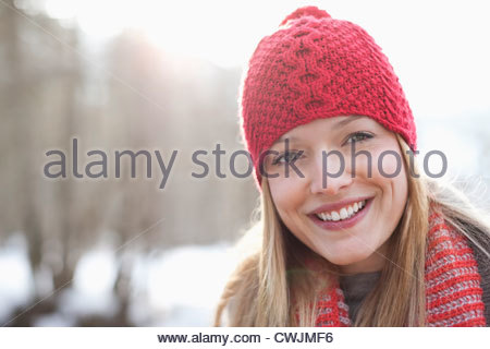 Close up portrait of smiling woman wearing red knit hat - Stock Photo