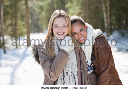 Portrait of smiling friends hugging in snowy woods - Stock Photo
